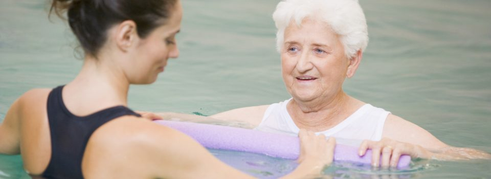 Woman trainer showing older woman hydrotherapy