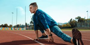 Runner athlete stretching on track