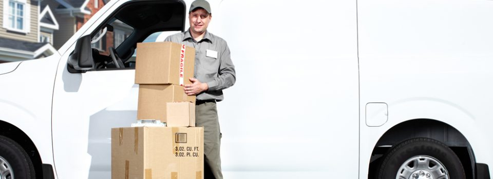 Delivery man standing beside van with boxes