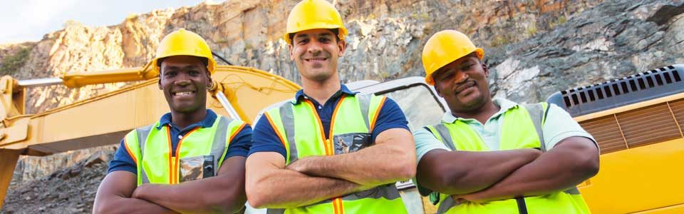 Three mine worker men with yellow hard hats